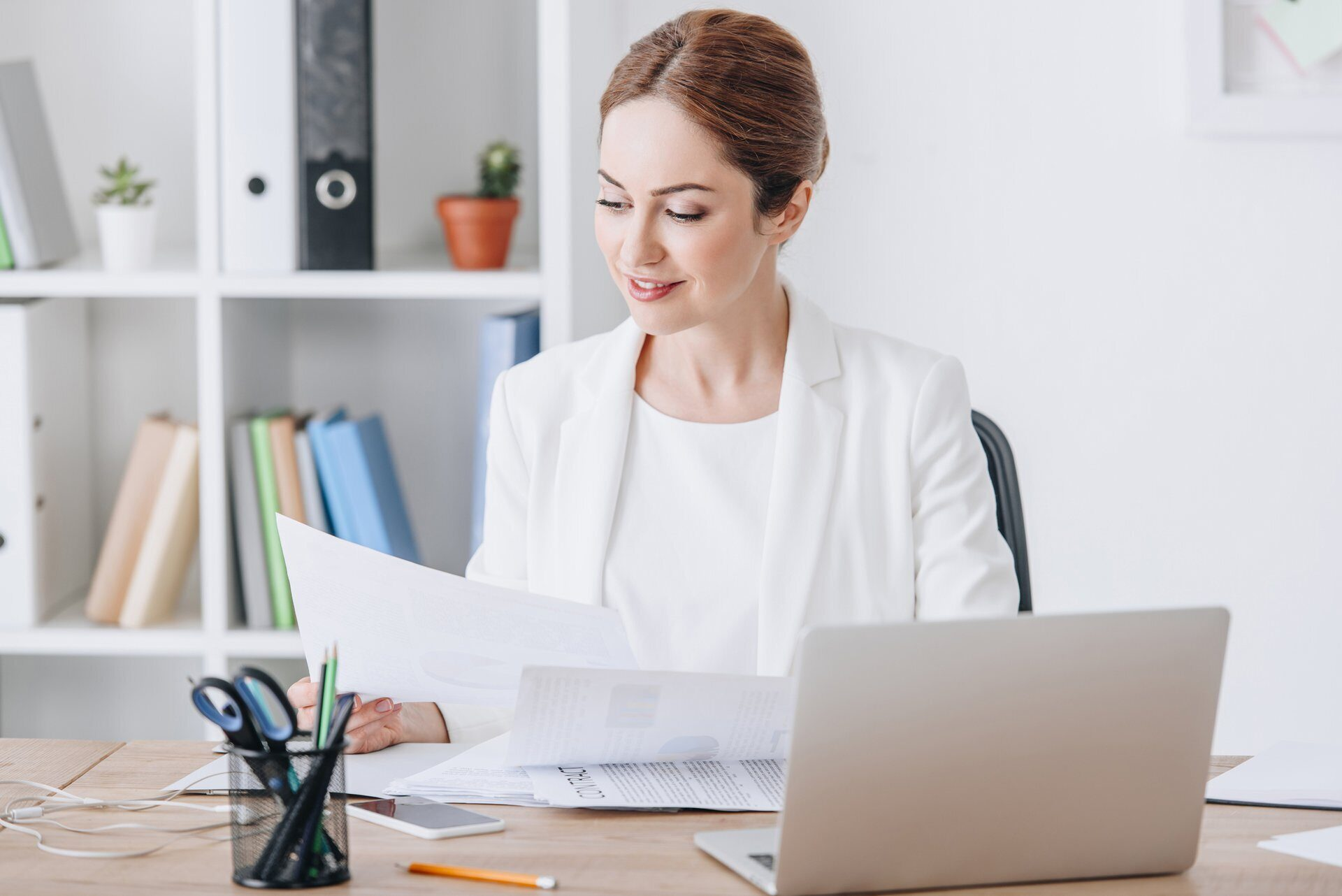 beautiful executive businesswoman working with documents and laptop at workplace in modern office